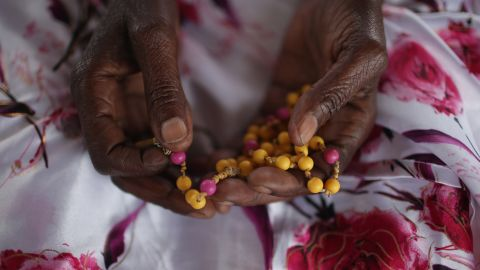Ophelia Nyiramagumeri holds a rosary in Kigali. It was given to her by her nephew, who was killed in the 1994 genocide.