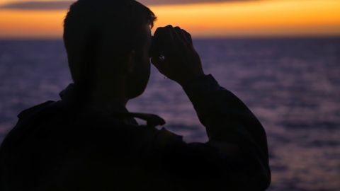 """A photo taken on April 7, 2014 and released by Australian Defence on April 11 shows Able Seaman Boatswains Mate Rothnie Marshall looking for any sign for the missing Malaysia Airways Flight MH370. Australian Prime Minister Tony Abbott said he is """"very confident"""" that signals detected in the search for Flight MH370 are from the aircraft's black box, whose batteries are waning fast more than a month after the plane vanished."""