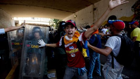 A protester shouts for fellow demonstrators to not attack the National Police trapped under a highway with protesters during clashes on April 12.