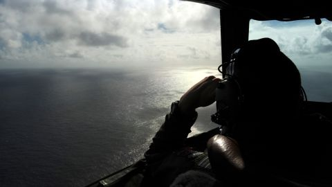A member of the Royal New Zealand Air Force looks out of a window while searching for debris from the missing Malaysia Airlines Flight 370 over the Indian Ocean off the coast of western Australia on Sunday, April 13.