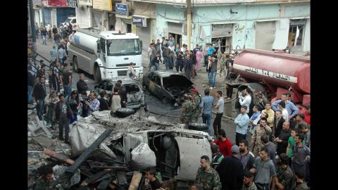 Security and emergency medical personnel work at the site of a car bomb explosion Monday, April 14, in the Ekremah neighborhood of Homs.