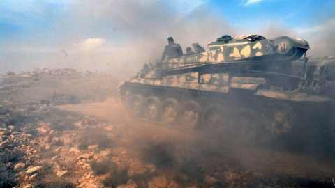 In this photo released by the state-run SANA news agency, Syrian forces take positions during clashes with rebels near the town of Rankous, Syria, on Sunday, April 13.