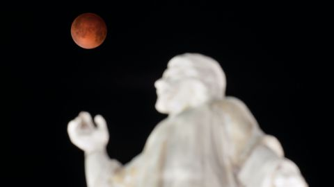 """A """"blood moon"""" rises over the El Salvador del Mundo monument in San Salvador early Tuesday, April 15, 2014, as a total lunar eclipse attracts sky gazers across the Americas. In a total lunar eclipse, the full moon turns a coppery red as it passes into Earth's shadow. """"It's like seeing all the sunsets on Earth projected on the moon at once,"""" says Indra Petersons of CNN's """"New Day."""""""