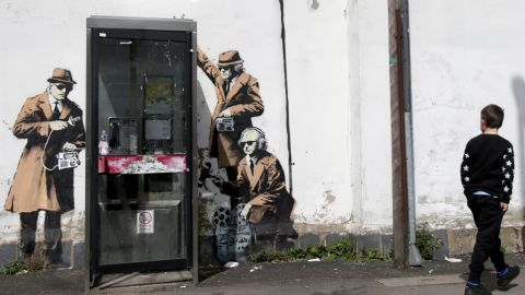 A boy walks past graffiti street art believed to be by Banksy in April 2014. The image depicts men in trench coats and dark glasses holding old-fashioned listening equipment -- apparently a commentary on government surveillance. The artwork appeared on the side of a house in Cheltenham near the Government Communications Headquarters, the UK equivalent of the National Security Agency.
