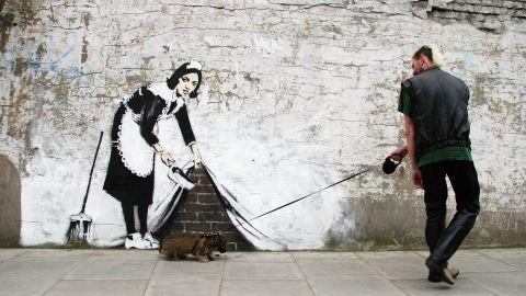 A man walks past a Banksy piece in London in 2006.