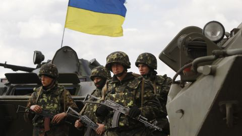 Ukrainian soldiers stand near APCs, that fly a Ukrainian flag, as the Ukrainian army troops receive ammunition  in a field on the outskirts of Izyum, Eastern Ukraine, Tuesday, April 15, 2014. An Associated Press reporter saw at least 14 armored personnel carriers with Ukrainian flags, one helicopter and military trucks parked 40 kilometers (24 miles) north of the city of Slovyansk on Tuesday. (AP Photo/Sergei Grits)