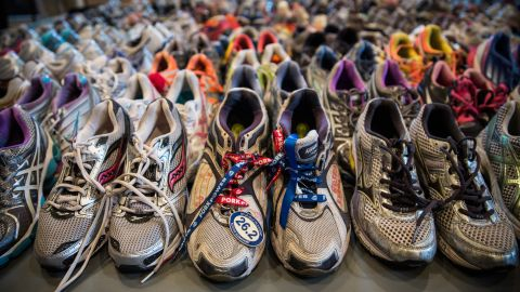 """Running shoes are laid out in a display at the Boston Public Library. It's called """"Dear Boston: Messages from the Marathon Memorial."""""""