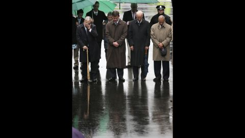 """From left, former Boston Mayor Tom Menino, Boston Mayor Martin Walsh, Vice President Joe Biden and Massachusetts Gov. Deval Patrick lower their heads for a moment of silence during the tribute. """"America will never, ever, ever stand down,"""" Biden said during the ceremony. """"We are Boston. We are America. We respond, we endure, we overcome and we own the finish line."""""""