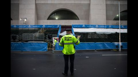 A Boston police officer waves traffic across the finish line.