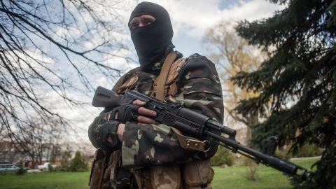 A masked gunman stands guard near tanks in Slovyansk on Wednesday, April 16.
