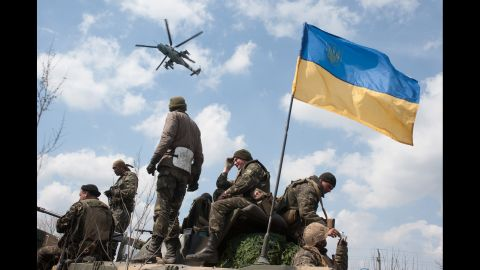 A Ukrainian helicopter flies over a column of Ukrainian Army combat vehicles on the way to Kramatorsk, Ukraine, on April 16.