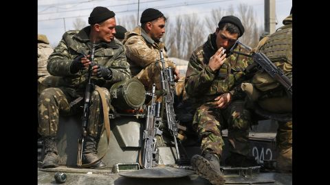 Ukrainian soldiers sit atop combat vehicles on their way to Kramatorsk.