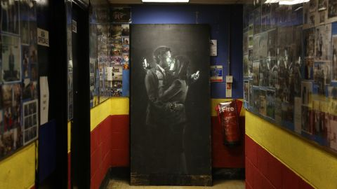 """A Banksy work appears at a youth center in Bristol, England, in April 2014. Called """"<a href=""""http://www.cnn.com/2014/04/16/world/europe/uk-art-banksy-removed/index.html"""">Mobile Lovers</a>,"""" it features a couple embracing while checking their cell phones. Members of the youth center took down the piece from a wall on a Bristol street and replaced it with a note saying the work was being held at the club """"to prevent vandalism or damage being done."""" The discovery came shortly after another image believed to be by Banksy surfaced in Cheltenham, England."""
