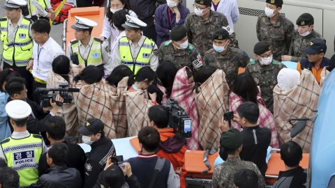 Officials escort rescued passengers April 16 in Jindo.