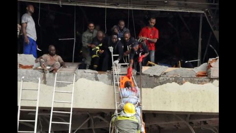 """Rescue workers help a wounded person from a U.N. building in Abuja, Nigeria, on August 26, 2011. The building was rocked by a bomb that killed at least 23 people, leaving others trapped and causing heavy damage. Boko Haram had claimed responsibility for the attack in which a Honda packed with explosives <a href=""""http://www.cnn.com/2011/WORLD/africa/08/31/nigeria.attack.al.qaeda/index.html"""">rammed into the U.N. building</a>, shattering windows and setting the place afire."""