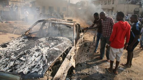 """Men look at the wreckage of a car after a bomb blast at St. Theresa Catholic Church outside Abuja on December 25, 2011. A string of bombs struck churches in five Nigerian cities,<a href=""""http://www.cnn.com/2011/12/25/world/africa/nigeria-church-bombing/index.html""""> leaving dozens dead and wounded on the Christmas holiday</a>, authorities and witnesses said. Boko Haram's targets included police outposts and churches as well as places associated with """"Western influence."""""""