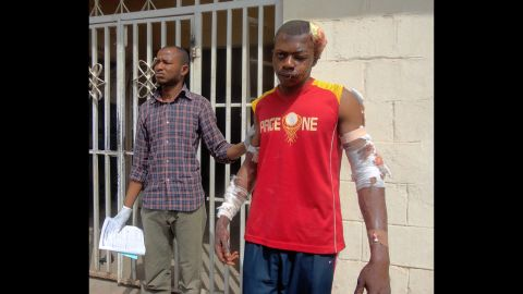 """A paramedic helps a young man as he leaves a hospital in the northern Nigerian city of Kano on January 21, 2012. A spate of bombings and shootings left more than 200 people dead in Nigeria's second-largest city. Three days later, a joint military task force in Nigeria <a href=""""http://www.cnn.com/2012/01/24/world/africa/nigeria-attacks/"""">arrested 158 suspected members</a> of Boko Haram."""
