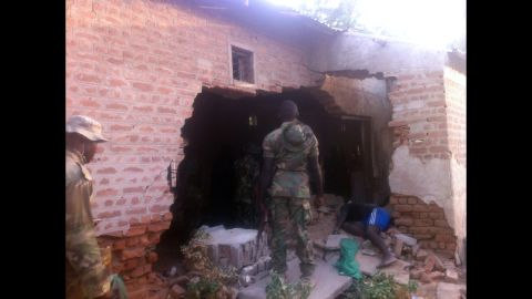 """A soldier stands in front of a damaged wall and the body of a prison officer killed during an attack on a prison in the northeastern Nigerian town of Bama on May 7, 2013. Two soldiers were killed <a href=""""http://edition.cnn.com/2013/05/09/world/africa/nigeria-violence/index.html"""">during coordinated attacks on multiple targets</a>. Nigeria's military said more than 100 Boko Haram militants carried out the attack."""