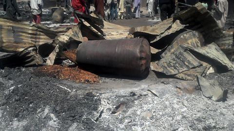 """Police officers stand guard in front of the burned remains of homes and businesses in the village of Konduga on February 12, 2014. Suspected Boko Haram militants<a href=""""http://edition.cnn.com/2014/02/12/world/africa/nigeria-unrest/""""> torched houses in the village,</a> killing at least 23 people, according to the governor of Borno state on February 11."""