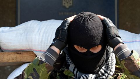A masked man stands guard outside a regional administration building seized by pro-Russian separatists in Slaviansk, Ukraine.