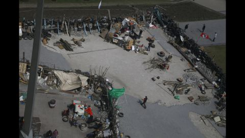 People walk around barricades April 18 set up at the regional administration building that was seized earlier in Donetsk.