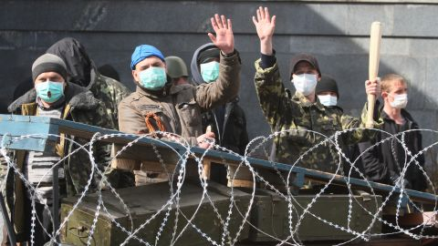 Pro-Russian activists guard a barricade set at the Ukrainian regional Security Service building on the eastern city of Donetsk on April 7, 2014.