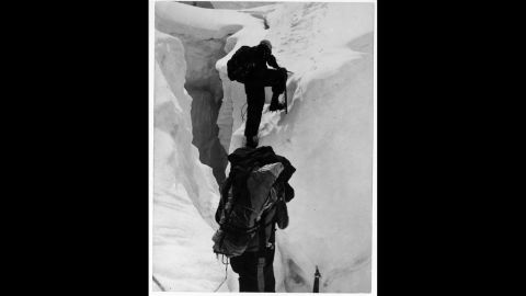 """Hillary and Nepalese-Indian mountaineer Tenzing Norgay climb beyond a crevasse on Mount Everest in 1953. Upon meeting George Lowe, who had climbed up to meet the descending duo, Hillary reportedly exclaimed, """"Well George, we knocked the bastard off!"""""""