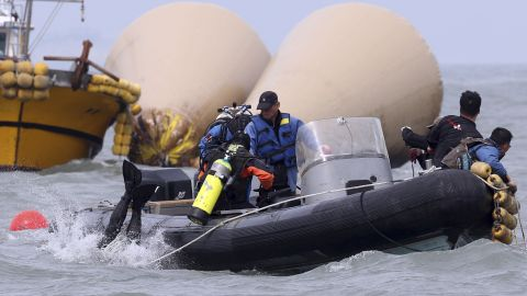 Divers jump into the water on April 21 to search for passengers near the buoys that mark the site of the sunken ferry.