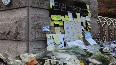 Post-it notes pile up in front of the sign at the gate of Danwon High School in Ansan, South Korea.