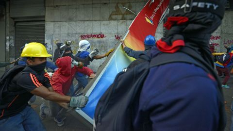Demonstrators destroy a bank sign in Caracas during a protest against the government on Sunday, April 20.