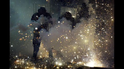 Police officers shield themselves from fireworks thrown by protesters in Caracas on April 20.