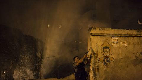 A police officer patrols the area among the smoke from burning barricades.