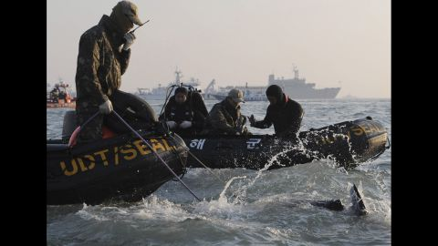 Search personnel dive into the sea on Wednesday, April 23.