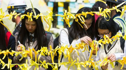 Caption:Schoolchildren tie yellow ribbons symbolising hope for the safe return of missing passengers on the 'Sewol' ferry onto the roadside of a main gate at Danwon high school on April 24, 2014. The body of a high school student who made the first distress call from a sinking South Korean ferry was recovered from the submerged vessel on April 24, news reports said. AFP PHOTO/ KIM DOO-HO (Photo credit should read KIM DOO-HO/AFP/Getty Images)