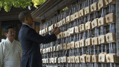 Obama places a prayer tablet on the Votive Tree at the Meiji Shrine.