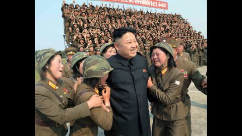 In this photo released Thursday, April 24, by the Korean Central News Agency, Kim smiles with female soldiers after inspecting a rocket-launching drill at an undisclosed location.