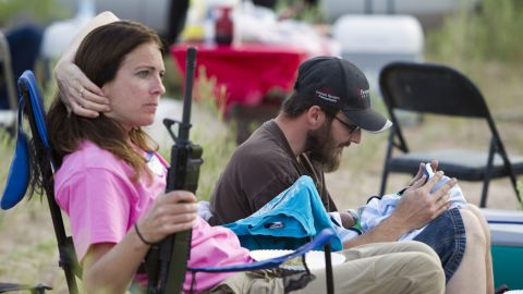 """Chris Shelton of Las Vegas interacts with his 1-week-old son as his mother Shelley Shelton holds his rifle during a Bundy family """"Patriot Party"""" near Bunkerville, Nevada, on April 18."""