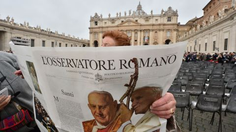 A woman reads a newspaper before the start of the canonization Mass on April 27.