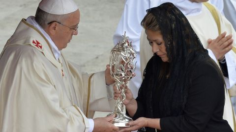 Floribeth Mora of Costa Rica, who claims she was cured of a serious brain condition by a miracle attributed to the late Pope John Paul II, hands the relic of John Paul II to Pope Francis during the canonization Mass for Popes John XXIII and John Paul II at the Vatican on Sunday, April 27.