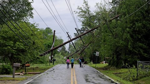 Residents walk along a Tupelo street on April 28.