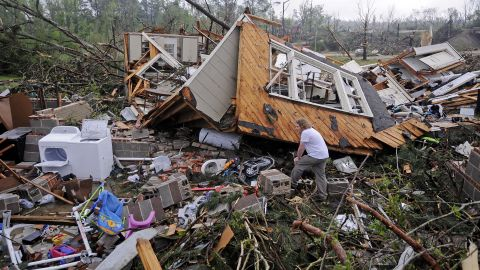 Kevin Barnes searches the remains of his home in Tupelo on April 29.