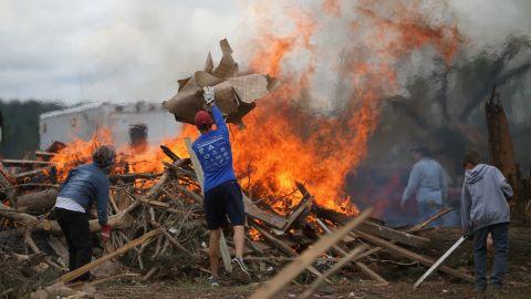 Volunteers throw tornado debris on a burn pile in Vilonia, Arkansas, on April 30.