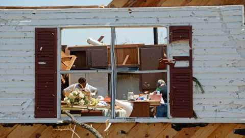 Bobbi Leggon and Sudie Carter work to salvage items from a friend's home in Tupelo on April 29.