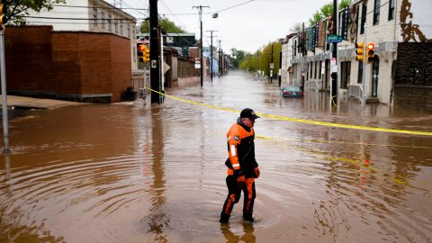 Marine unit police officer Robert Jonah walks through flood waters from the Schuylkill River on Main Street, Thursday, May 1, 2014, in the Manayunk neighborhood of Philadelphia. Heavy rains sent rivers and streams over their banks, flooding low-lying areas in Philadelphia and surrounding counties and forcing the evacuation of several apartment complexes and many rescues. (AP Photo/Matt Rourke)