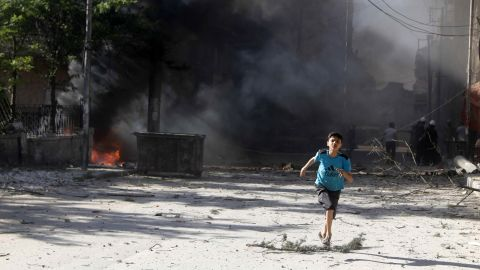 A boy runs in Aleppo on Sunday, April 27, after what activists said were explosive barrels thrown by forces loyal to al-Assad.