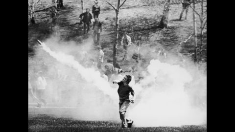 A student throws a tear gas canister back at National Guardsmen. After several standoffs, the troops headed back up a hill in the direction of the ROTC building. As they reached the top, they turned toward the demonstrators and opened fire.