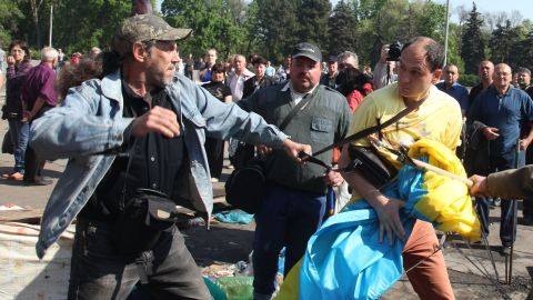 Pro-Russian activists beat a pro-Ukraine supporter trying to save the Ukrainian flag that was removed from a flagpole outside the burned trade union building in Odessa.