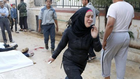 A woman runs after two barrel bombs were thrown, reportedly by forces loyal to Syrian President Bashar al-Assad in Aleppo on May 1.