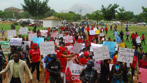 """Former Nigerian Education Minister and Vice-President of the World Bank's Africa division (2nd L) Obiageli Ezekwesilieze speaks as she leads a march of Nigeria women and mothers of the kidnapped girls of Chibok, calling for their freedom in Abuja on April 30, 2014. Nigerian protesters marched on parliament today to demand the government and military do more to rescue scores of schoolgirls kidnapped by Boko Haram Islamists more than two weeks ago. Dubbed """"a million woman march"""" and promoted on Twitter under #BringBackOurGirls, the protest was not expected to draw a massive crowd and turn-out was hindered by heavy rain in the capital Abuja. But several hundred women and men, mostly dressed in red, marched through the rain towards the National Assembly carrying placards that read """"Find Our Daughters."""""""