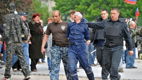 Pro-Russian militiants carry an man with his eyes covered outside the regional state building they seized in the eastern Ukrainian city of Donetsk on May 5, 2014.